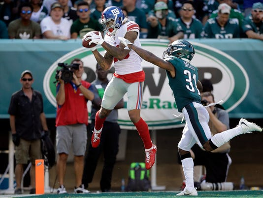 FILE - In this Sept. 24, 2017, file photo, New York Giants' Odell Beckham Jr., left, catches a touchdown against Philadelphia Eagles' Jalen Mills during the second half of an NFL football game in Philadelphia. Tampa Bay Buccaneers' Mike Evans wants no part of a debate about whether he or Beckham is the best young receiver in the NFL. (AP Photo/Matt Rourke, File)