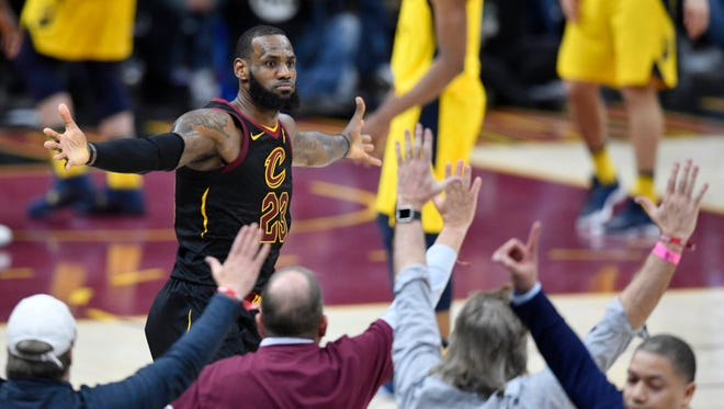 Cleveland Cavaliers forward LeBron James (23) and head coach Tyronn Lue, right, celebrates James' game-winning, three-point basket in the fourth quarter against the Indiana Pacers in game five of the first round of the 2018 NBA Playoffs at Quicken Loans Arena.