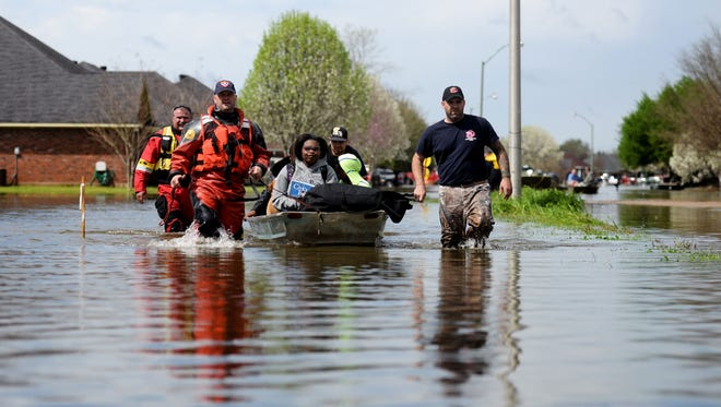 People are boated out of Golden Meadows subdivision with the help of local firefighters in Bossier City, Louisiana Thursday afternoon, March 10, 2016.