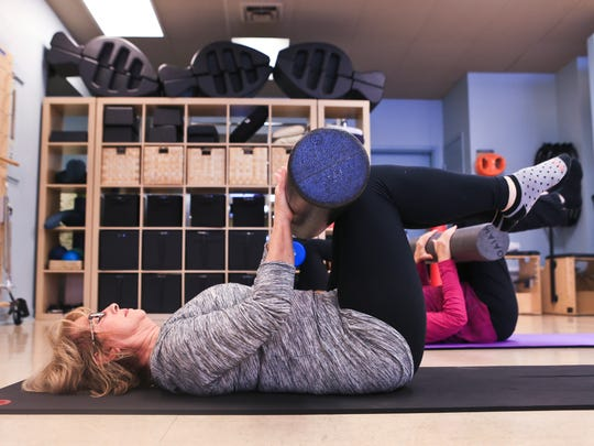 Phyllis Green lifts her legs in an exercise during a Buff Bones class at Pilates Village in St. Matthews. The class combines Pilates along with light weights to help strengthen core muscles as well as build stronger bones.