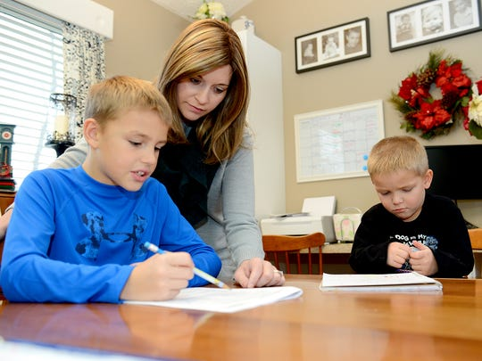 Annie Scholten helps her son Eli, 8, with his homework in their Williamston home Wednesday, December 9, 2015 as youngest son Logan, 4, colors. Scholten was diagnosed with terminal cancer and was told she had less than a year to live. With the news, the Williamston community has rallied around to help the family.