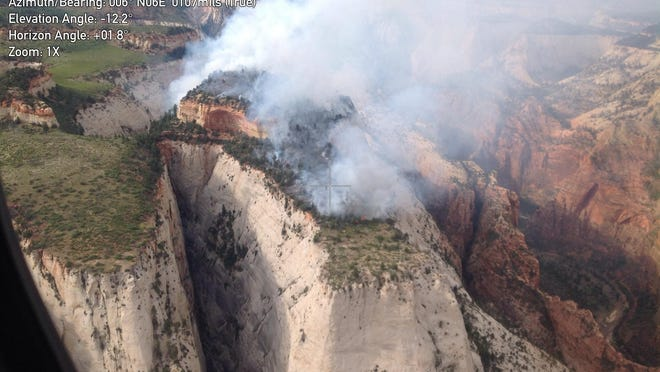 An overhead shot taken from a helicopter shows the Cathedral Fire burning atop a mesa in Zion National Park on Saturday. The fire has burned much of the mesa top, forcing the closure of popular nearby trails, including the hike to Angels Landing.