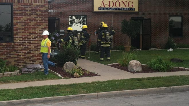 Des Moines firefighters and MidAmerican Energy workers move about the A Dong restaurant building Sunday after an apparent kitchen fire caused significant smoke damage.