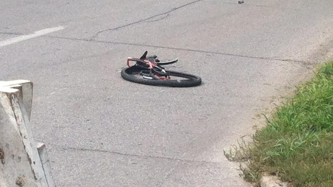Part of a bicycle involved in a hit-and-run crash rests on Grand Avenue in Des Moines on Aug. 16, 2015.