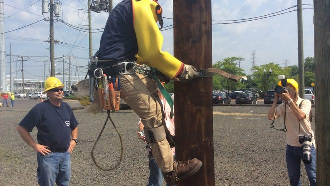 Jason Blough, an apprentice lineman at PSE&G, climbs a utility pole with all his gear, including heavy rubber gloves covered with leather gloves, a hard hat, goggles, rubber sleeves to protect his arms, and a tool belt weighing 30 pounds or more.