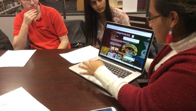 Daniel Falk, 17, of East Brunswick, a junior at Torah Academy of Bergen County, and Sakshi Roongta, 15, a sophomore at East Brunswick High School, look on as Cionna Morges, 15, also a sophomore at East Brunswick High School, reveals the new website she created for Dobby's Favorite Sock, the East Brunswick Public Library's chapter of The Harry Potter Alliance.