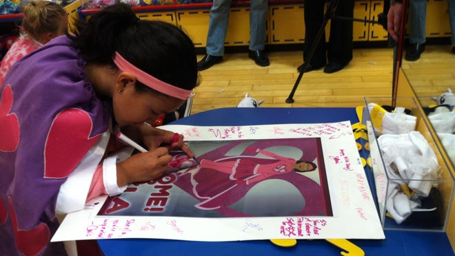 Super Sheyla Florian, 7, of Des Moines signs a poster that was presented to her at Build-A-Bear Workshop .