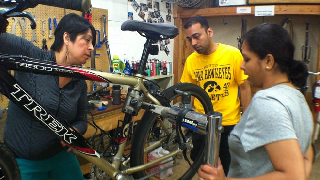 Iowa City Bike Library volunteer Natalia Espina, left, explains basic bike maintenance to patrons Aniruddha and Shruti Deshpande on Saturday.
