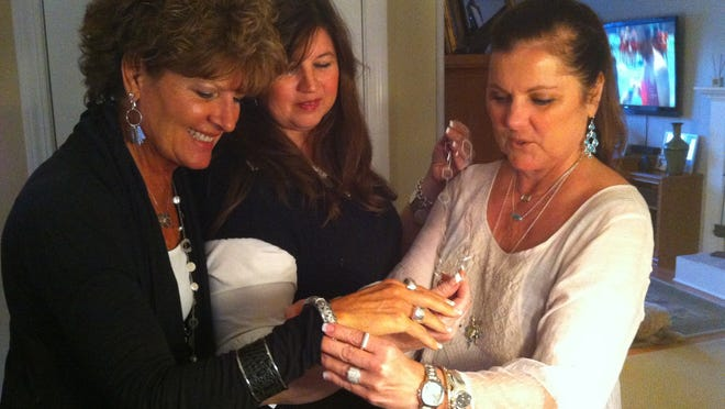 Silpada rep Melanie Campbell of Fairport, center, looks on as Jody Belcher, left, and Chris McCartney, right, try on jewelry at a Fairport party.