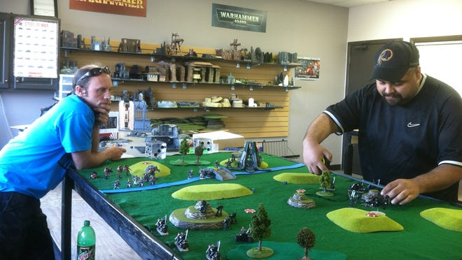 """Eric """"Dragon"""" Brychta and Tom Koustrup play a war game at Universal Bits and Games on a recent evening. The store allows customers to play at no cost, and its owner would like more business."""