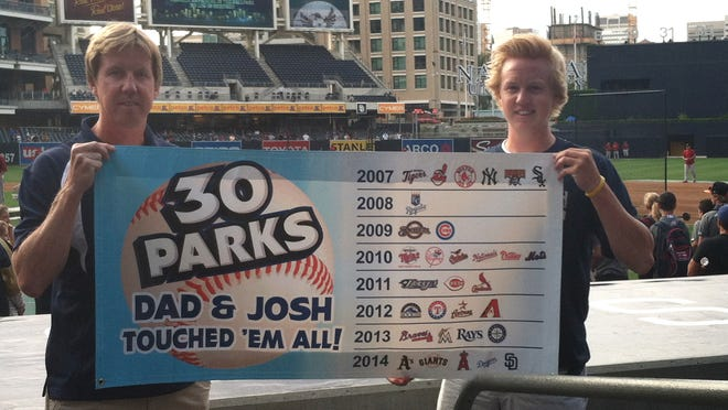 "Dan ""Dugan"" Bjorlin (left) and his son Josh hold a banner commemorating the completion of their major league ballpark tour on June 27 at San Diego's Petco Park."