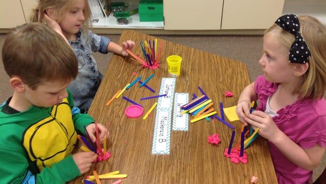 Woodside kindergarten students Connor Vine, Sydney Koch and Lydia Tamminga explore stick house designs.