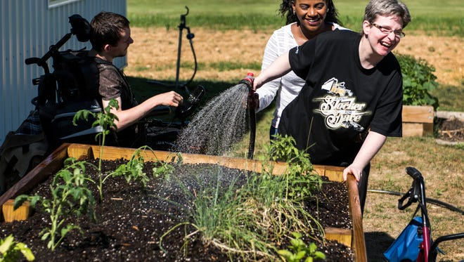Brenda Calhoun, a direct support professional, helps Kim Robards water plants in a raised garden bed outside of the Hugh Edward Sandefur Center in Henderson, Kentucky, on Tuesday, June 20, 2017. The center serves as a facility for adults with intellectual and developmental disabilities and provides training programs to the participants. The new gardening project aims to teach them how to grow and raise crops in hopes to sell them in the future.