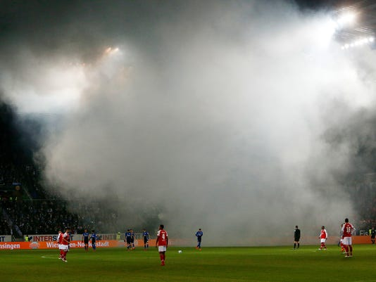 Players wait for kick off after Schalke fans lit bengals prior to a German first division Bundesliga soccer match between FSV Mainz 05 and FC Schalke 04 in Mainz, Germany, Friday, March 9, 2018.(AP Photo/Michael Probst)