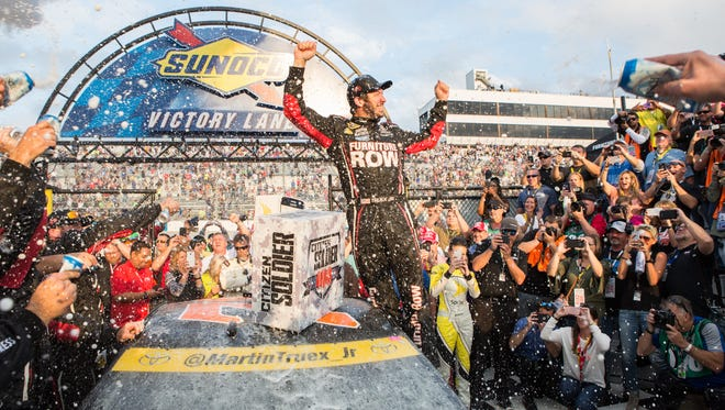Martin Truex Jr celebrates a successful race in Victory Lane after completing the Citizen Soldier 400 at Dover International Speedway on Sunday, Oct. 2, 2016.