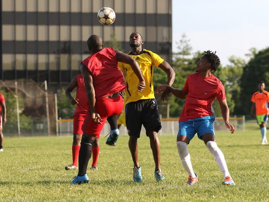 Players from Cameroon (red jerseys) and Mauritania (yellow) play soccer in Forest Park Sunday May 29, 2016. Teams from several countries will be playing in the World Refugee Day Cup Soccer Tournament at Withrow High School Saturday June 4 to celebrate World Refugee Day.