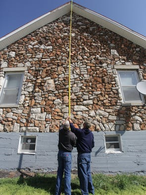 Darrin Tilton, left, and Aaron Tilton of Tilton and Sons House Moving measure Timmons Temple on Tuesday, April 15, 2014.