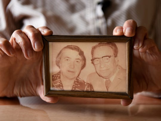 Claudia Liberchuk holds a portrait of her parents,