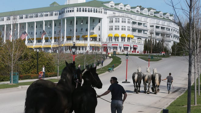 In a photo from Wednesday, May 6, 2015 in Mackinac Island Mich., horses are lead by the Grand Hotel to their stables after arriving on the island by ferry.