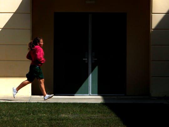 Island Coast High School freshman wrestler Jenna Swift runs around the Cape Coral school Monday.