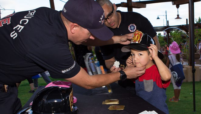 In this file photo, Jordan Ruiz, 6, gets fitted with a Las Cruces Fire Department helmet during the National Night Out event held at the Downtown Plaza on August 1, 2017.