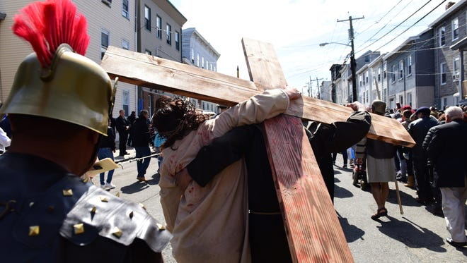 Ricardo Martinez, as Jesus, is helped while carrying the Cross during the performance of the Passion of Christ Friday morning April 14, 2017.