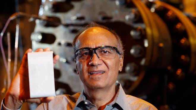 In this Oct. 9, 2014 photo, General Electric Chief Scientist Krishan Luthra poses with a ceramic matrix composite turbine part in front of a combustion test rig at GE Global Research in NIskayuna, N.Y. Luthra's three decade-long effort to invent a tough and light new material is helping GE attract aircraft engine orders worth billions of dollars.(AP Photo/Mike Groll)