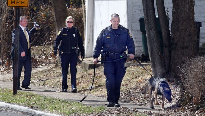 Cincinnati Police K-9 officer Jerry Hodges and his dog, Jones,  follow a track on Fairfax Avenue, Evanston, after a man with a gunshot wound was stopped in the area.