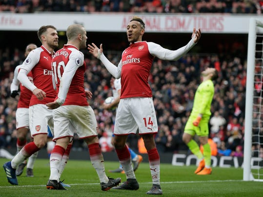 Arsenal's Pierre-Emerick Aubameyang, right, celebrates after scoring a penalty with Arsenal's Jack Wilshere, centre, and Arsenal's Aaron Ramsey during the English Premier League soccer match between Arsenal and Stoke City at the Emirates Stadium in London, Sunday, April 1, 2018. (AP Photo/Tim Ireland)