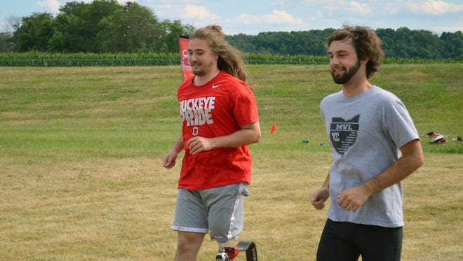 Zach Hanf (left) runs with former teammate Broc Wilkins in the annual Sheridan Alumni Cross Country Race last Saturday at Sheridan High School. Hanf, currently a senior at Ohio State, raced for the first time since losing part of his leg in a crash in October 2012.