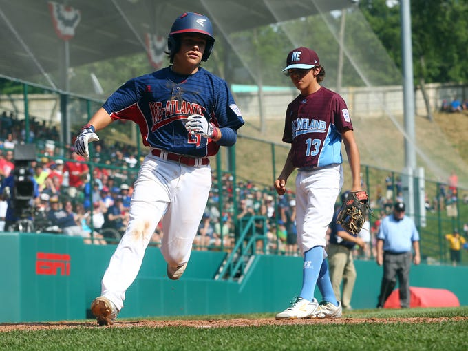 Holbrook Little League's Chris Cartnick scores on a