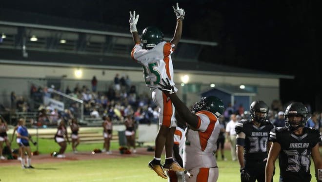 FAMU DRS' Terrence Cambridge lifts up Justin Stubbins in celebration of his touchdown against Maclay during their game at Maclay school on Friday, Oct. 20, 2017.