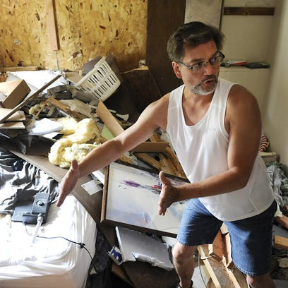 Tom Esplan shows photos in front of his home in Sauk Rapids on Monday that his brother took after a pickup crashed into his bedroom while he slept. Esplan was pinned underneath the pickup and says he is still troubled by the experience.