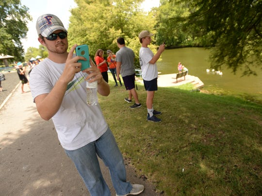 Austin Harrell aims his smartphone camera as he searches for Pokemon GO characters at the Duck Pond in Shreveport.