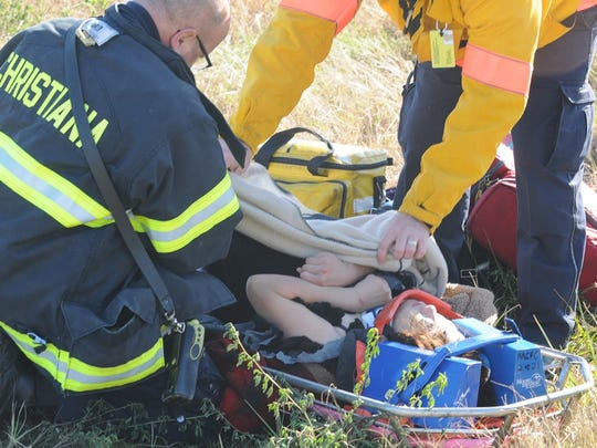 Firefighters and paramedics tend to a woman rescued from an SUV that went down an embankment and overturned in a retention pond in front of Christiana Mall Wednesday afternoon.  Bystanders helped free six people who were inside.