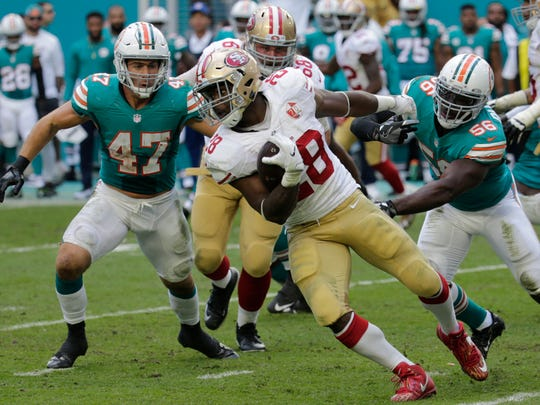 San Francisco 49ers running back Carlos Hyde (28) is stopped by Miami Dolphins outside linebacker Donald Butler (56), during the second half of an NFL football game, Sunday, Nov. 27, 2016, in Miami Gardens, Fla. To the left is Miami Dolphins middle linebacker Kiko Alonso (47). (AP Photo/Lynne Sladky)