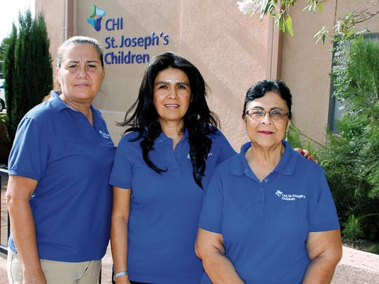 Bill Armendariz - Headlight Photo   Team Leader Mari Garcia, center, and her staff, Cruz Granado, left, and Dolores Valdez stand in front of the CHI St. Joseph's Children Office at 201 E Pine St. The Children's Health Initiative program came to Deming in February and is here to service first-time parents with in-home visits and referrals. They will host a grand opening and ribbon cutting at 1:30 p.m. on Sunday. The public is invited to learn more about CHI St. Joseph's Children.
