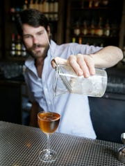 In this photo taken Tuesday, Aug. 19, 2014, bartender Chad Arnholt makes a cocktail called The Martinez using Old Tom Gin at the Trick Dog bar in San Francisco. Almost extinct, Old Tom has been getting a new lease on life as part of the overall rise of gin and the resurrection of classic cocktails.