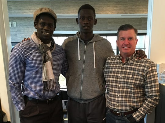 Peter Jok, middle, is flanked by two men who served as father figures for him in America: his older brother, Dau, left; and Mike Nixon, right.