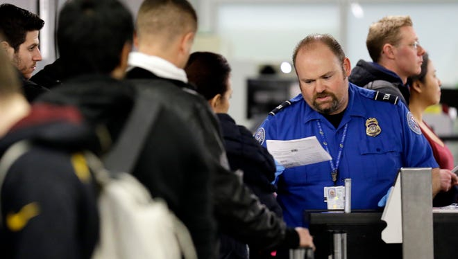 A TSA officer checks a passenger's airline ticket at Chicago O'Hare International Airport on Dec. 20, 2013.