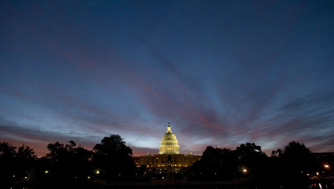 The US Capitol dome is seen at sunrise over Washington, D.C. on Wednesday. A fractured Congress is struggling to approve a stopgap spending bill that keeps government doors open after the current fiscal year ends next Monday.