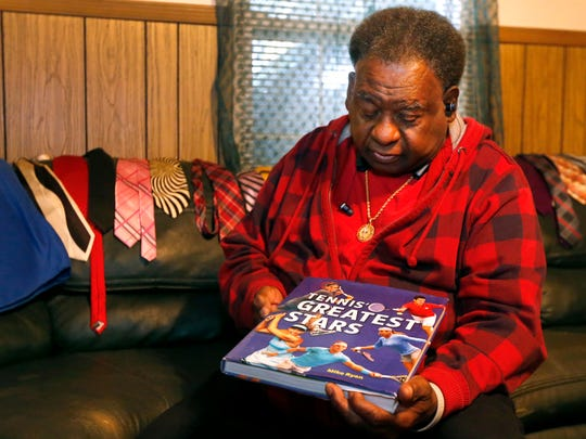 """Henry """"Dubie"""" Knox shows off a tennis book that was sent to him from Serena Williams and her foundation."""