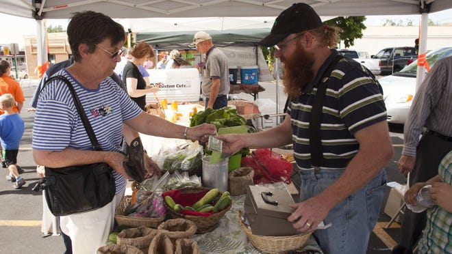 Myrna Mace from Cedar City buys fruit from Adam Nicoll at the Wednesday farmers market in Cedar City last year.
