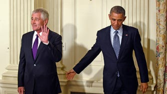 President Obama reaches to Defense Secretary Chuck Hagel following an announcement of Hagel's resignation during an event at the White House.