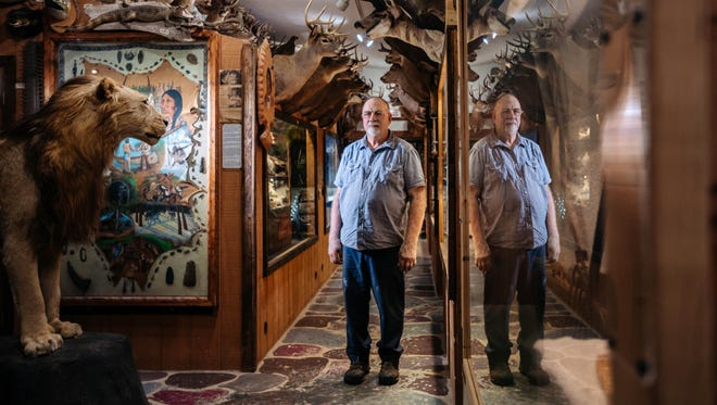 """Voss Guntzviller stands by the showcases he built using taxidermied animals at his Spirit of the Woods Museum in Williamsburg on Aug. 17, 2017. """"People said that man, this is like the Smithsonian of the north you know? It's stuff that you just don't see every day,"""" he said."""