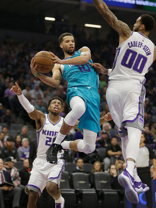 Charlotte Hornets guard Michael Carter-Williams, center, drives between Sacramento Kings' Buddy Hield, left, and Willie Cauley-Stein, during the first quarter of an NBA basketball game Tuesday, Jan. 2, 2018, in Sacramento, Calif. (AP Photo/Rich Pedroncelli)