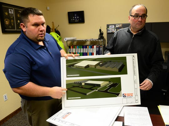 Gibsonburg Mayor Steve Fought, left, and village administrator Marc Glotzbecker hold diagrams showing what the new medical marijuana facility will look like.