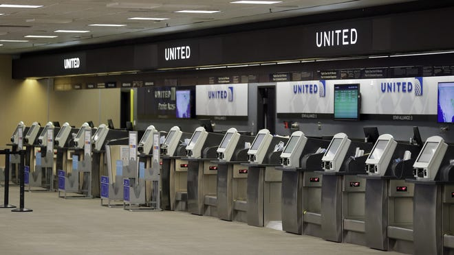 In this April 24, 2020 file photo, empty United Airlines ticket machines are shown at the Tampa International Airport in Tampa, Fla. United United Airlines will send layoff warnings to 36,000 employees - nearly half its U.S. staff - in the clearest signal yet of how deeply the virus outbreak is hurting the airline industry. United officials said Wednesday, July 8 that they still hope to limit the number of layoffs by offering early retirement, but they have to send notices this month to comply with a law requiring that workers get 60 days' notice ahead of mass job cuts.