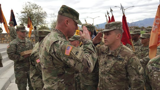 Maj. Gen. Terry McKenrick, left, hands out coins to
