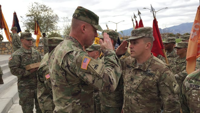 Maj. Gen. Terry McKenrick, left, hands out coins to soldiers from Fort Bliss' 2nd Brigade during the brigade's change of mission ceremony in December.